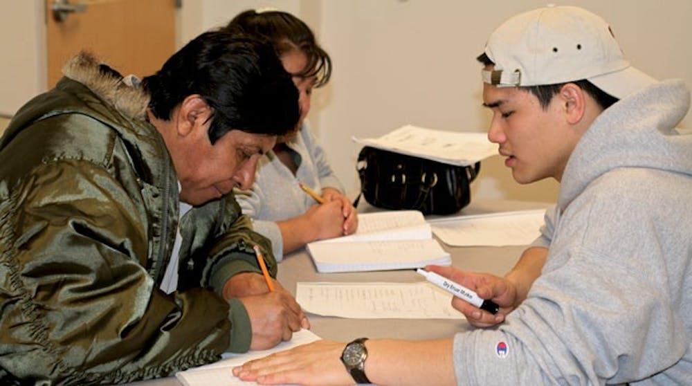 Russ Gong helps Arturo Martinez and Rasalienda Hatelpa with their english