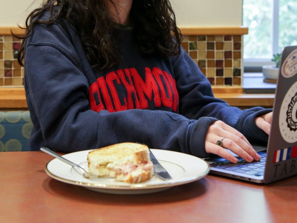 A patron at Passport Café enjoys their sandwich on a reusable ceramic plate. The use of glassware in the cafes is one of several new initiatives by University Dining Services in an effort to improve campus sustainability.