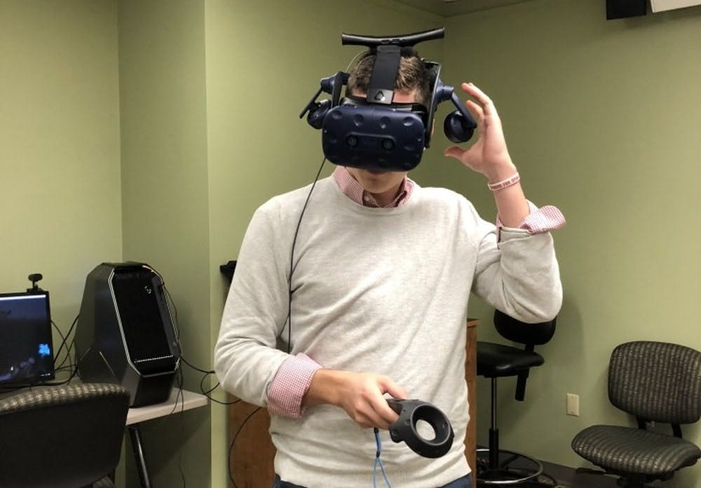 <p>Senior Grant Hinman, who works at the Technology Learning Center, tries on one of the virtual reality headsets.</p>