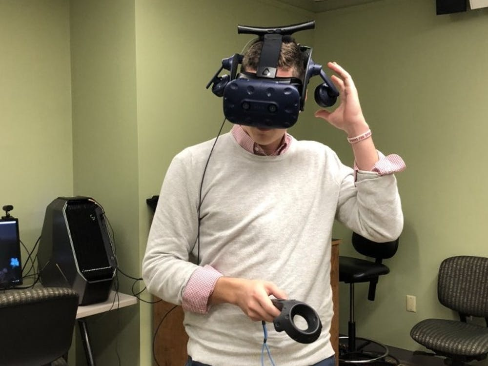 Senior Grant Hinman, who works at the Technology Learning Center, tries on one of the virtual reality headsets.
