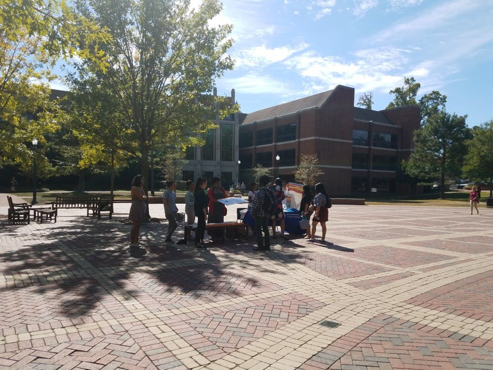 Participants of the Give Five, Take Five event on Fridayspeak to students about suicide prevention and sell donuts for Richmond's Out of the Darkness Walk.