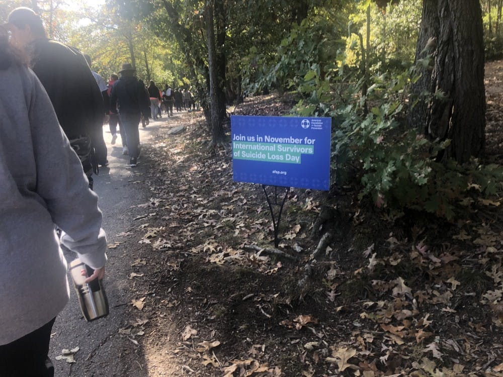 <p>A sign along the trail of the Out of Darkness walk advertises the next AFSP event.</p>