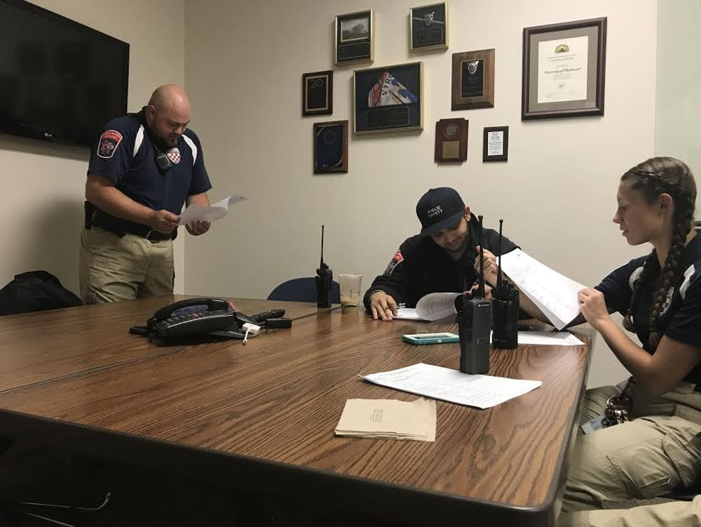 <p>PSAs Kyle Linardo, Ayush Malik and Maddie Bright debrief at the URPD headquarters before heading out for patrol.</p>