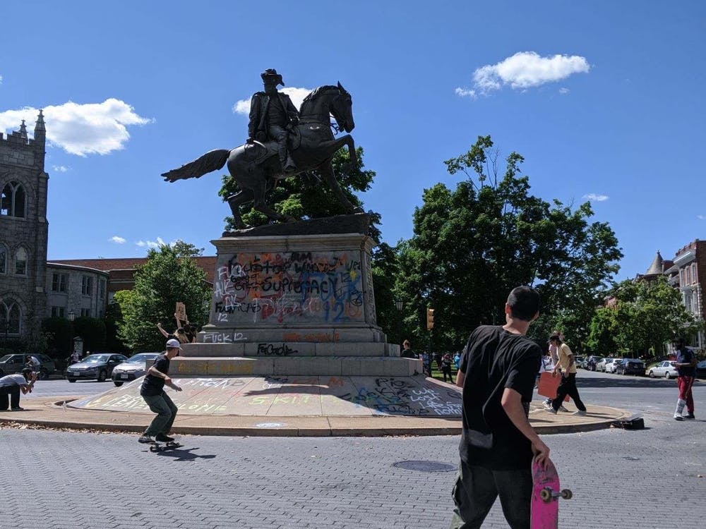 People skateboarding on and around the J.E.B. Stuart statue, now covered with graffiti, on Monument Avenue on May 31.