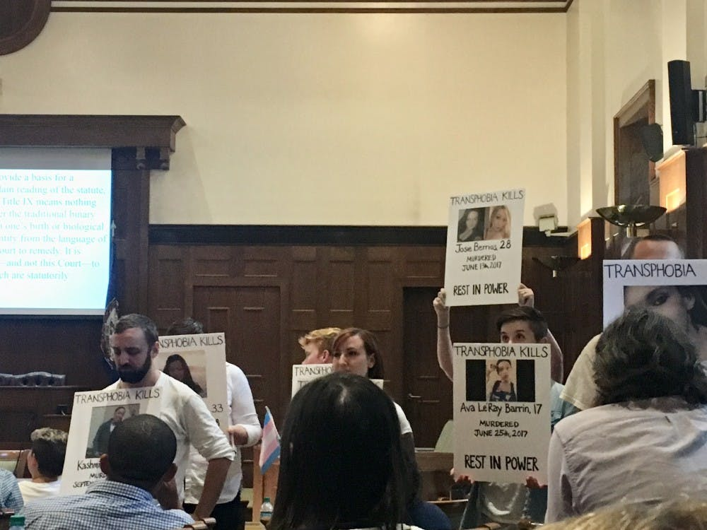 Student protesters in all white holding posters of transgender people who were either murdered or committed suicide due to transphobia during Ryan T. Anderson's talk at the law school.
