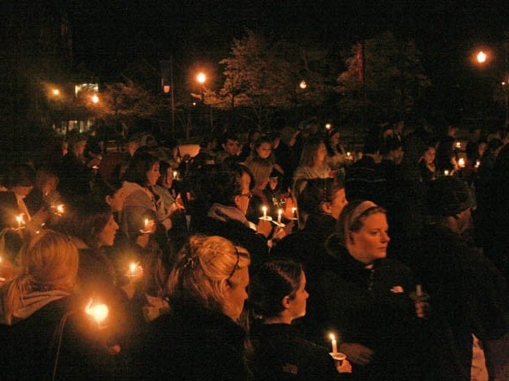 The many attendees of the Take Back the Night event Tuesday evening joined together at the end to light candles in the dark.