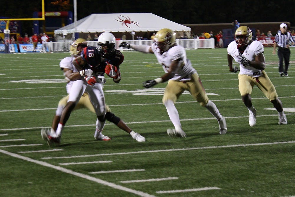 <p>Richmond wide receiver Dejon Brissett tries to break a tackle&nbsp;by two Elon defenders.</p>