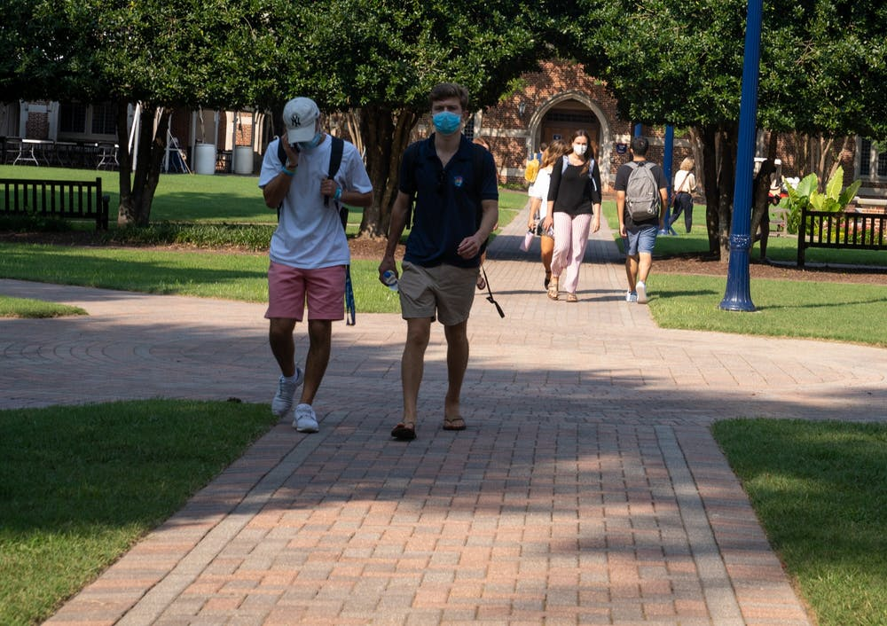 <p>Students walk in the Stern Quadrangle in between classes with their masks on.&nbsp;</p>