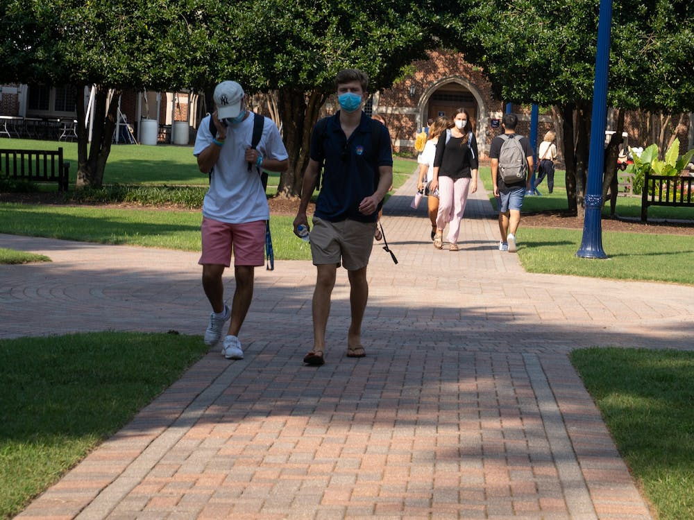 Students walk in the Stern Quadrangle in between classes with their masks on.