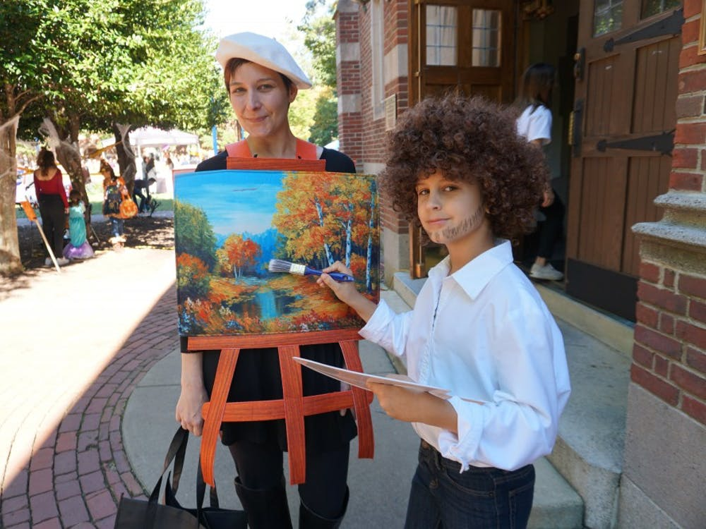 Laura Knouse, associate professor of psychology, and her son, Liam, dressed as Bob Ross and his painting.