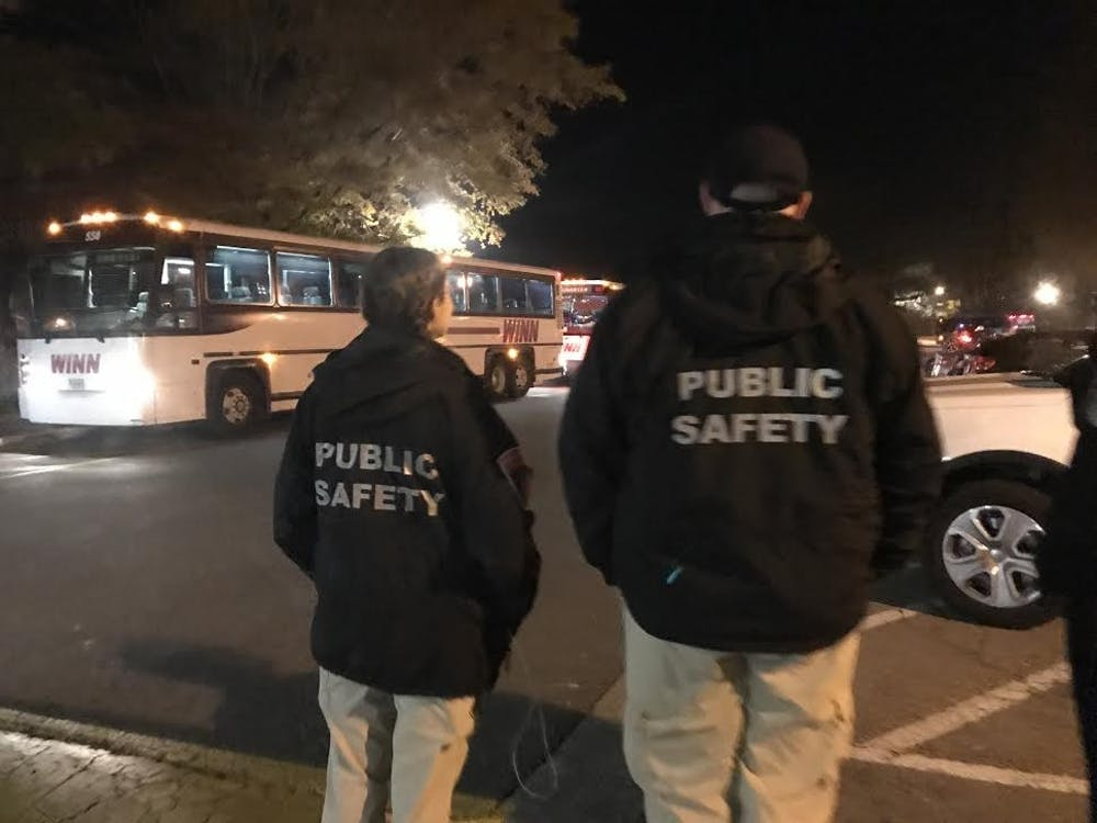 Bright and Linardo look on as buses carrying students from a social pull back onto campus.