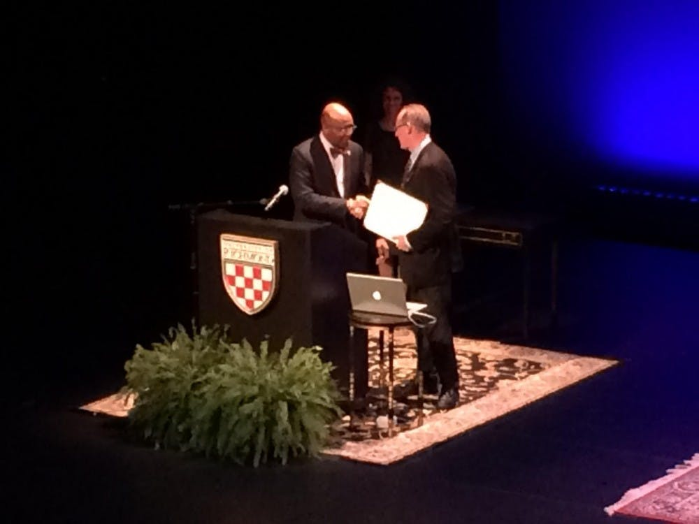 <p>Paul Farmer accepts an honorary doctorate degree from President Ronald Crutcher.</p>