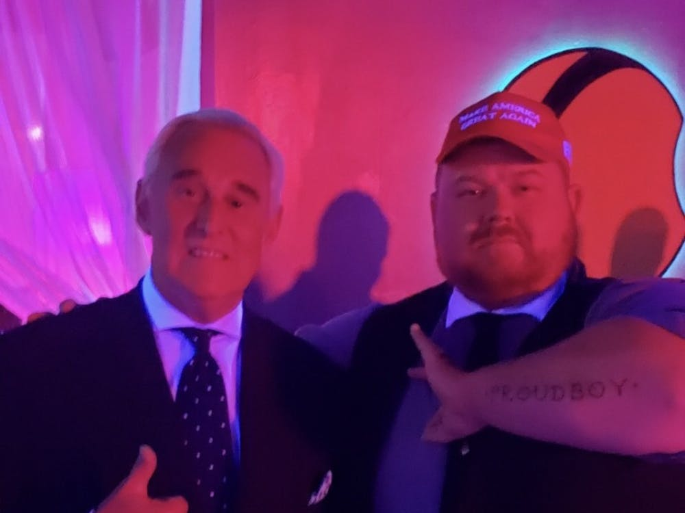 "Roger Stone (left) poses for a picture with Patrick, a member of The Proud Boys. Patrick is forming an ""Ok"" symbol with his hands, a sign that has become popular among white-supremacists since the 4-chan campaign ""Operation O-KKK."" He is also showing his ""Proud Boy"" tattoo on his forearm."