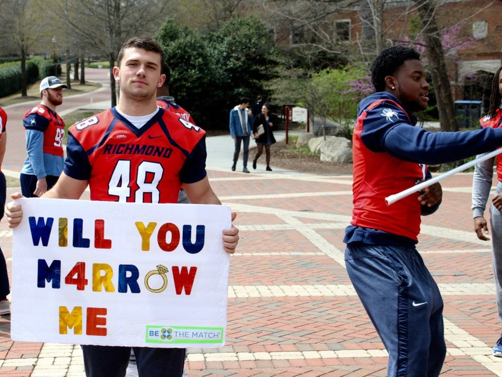 Football players recruit students to join the bone marrow registry in the Forum on April 11, 2018.