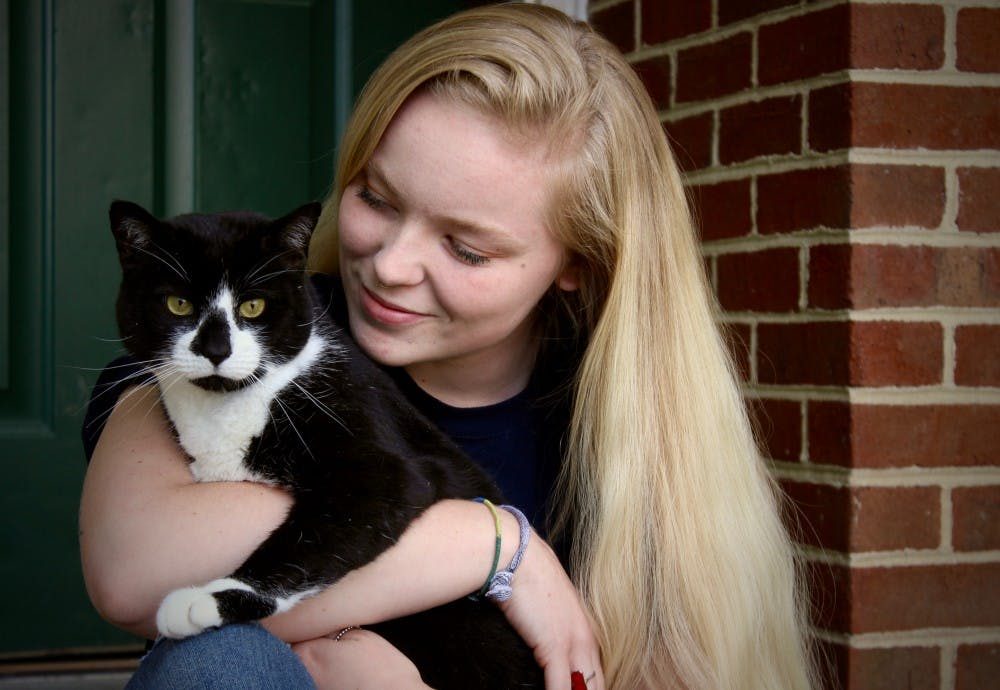 <p>Junior Brier Clough sits outside of her apartment with her cat, Tucker.</p>