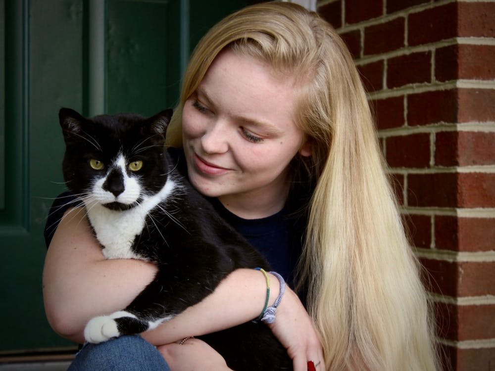 Junior Brier Clough sits outside of her apartment with her cat, Tucker.