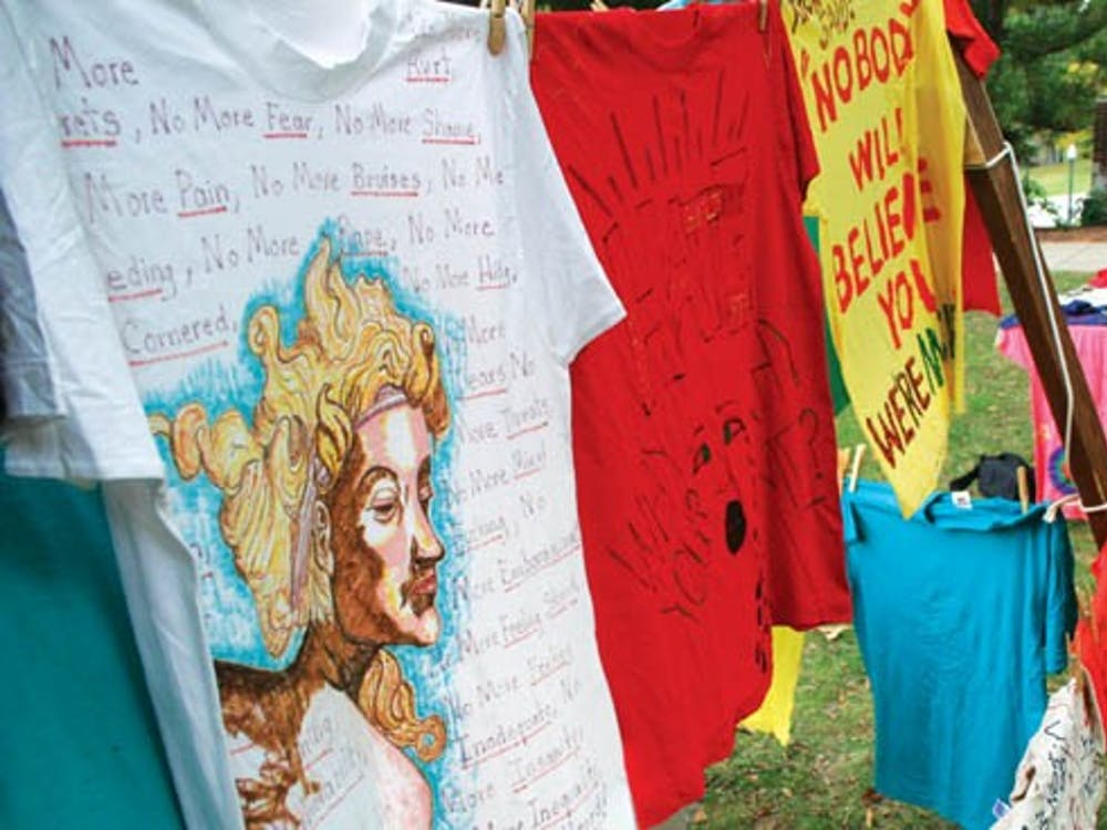 Sophomore Courtney Lund monitors a table promoting The Clothesline Project outside Boatwright Memorial Library Tuesday afternoon.  The project is aimed at addressing the issue of violence against women. It honors women survivors as well as victims of intimate violence.Students who were victims of domestic violence or knew victims could make shirts to hang on the line.