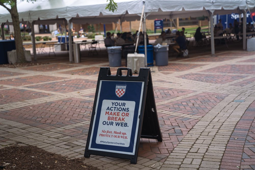 <p>A sign reminding students to adhere to distancing guidelines stands outside the cafeteria tent in the forum on Sept. 8.</p>