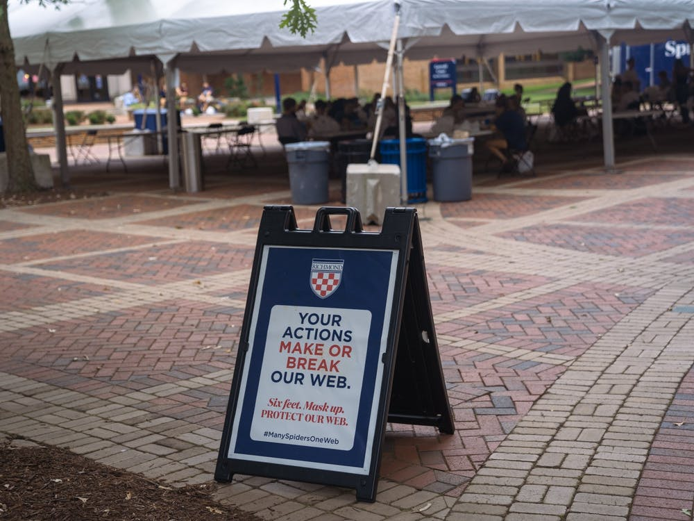 A sign reminding students to adhere to distancing guidelines stands outside the cafeteria tent in the forum on Sept. 8.