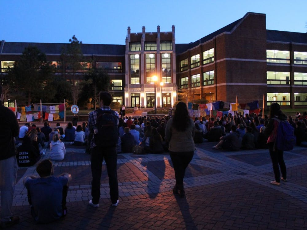 Students gather to listen as survivors of sexual violence and their allies share their stories at Take Back the Night in the Forum.