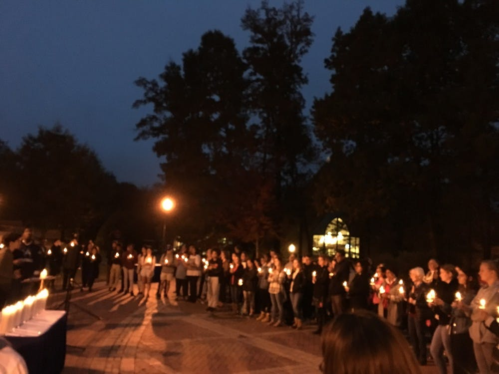 """<p>Students and community members reflect in memory of recent victims of violence as a cappella group Couer-du-Roi sings """"Imagine"""" by John Lennon.</p>"""