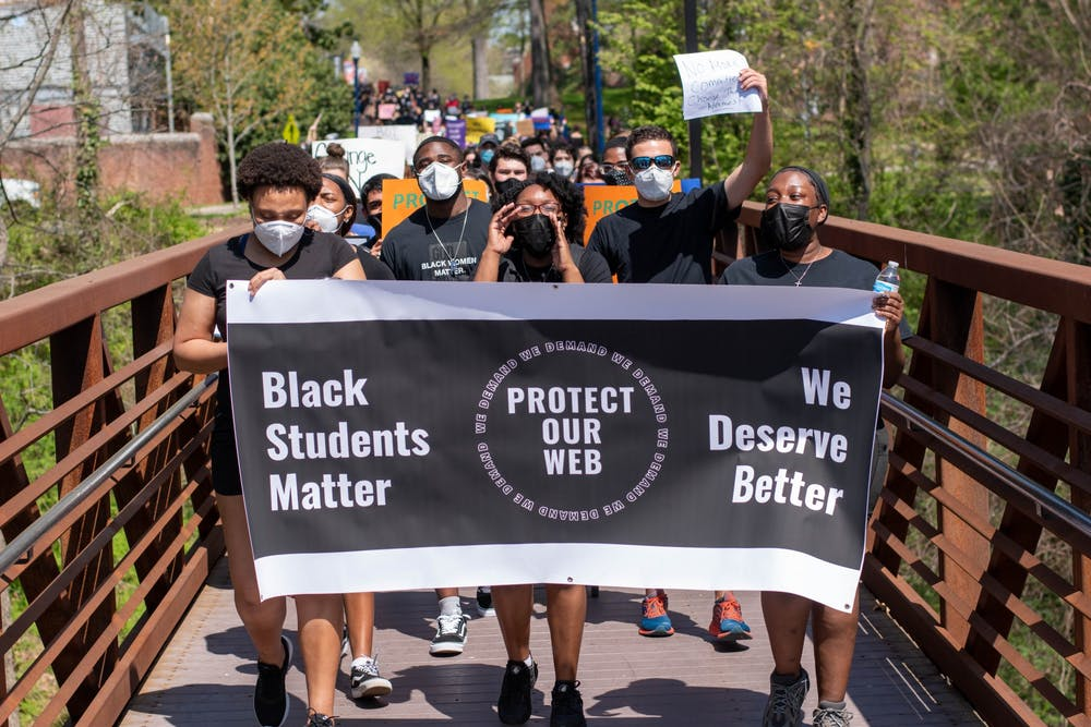 "<p>Protesters march across the bridge leading into parking lot U21. Leaders of the protest carry a Protect Our Web banner that reads ""Black Students Matter"" and ""We Deserve Better.""</p>"