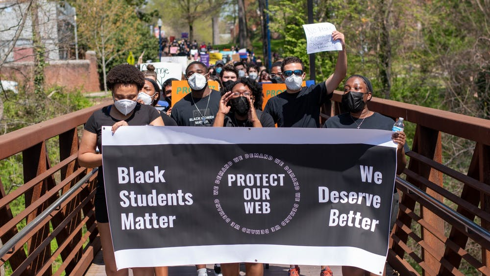 """Protesters march across the bridge leading into parking lot U21. Leaders of the protest carry a Protect Our Web banner that reads """"Black Students Matter"""" and """"We Deserve Better."""""""