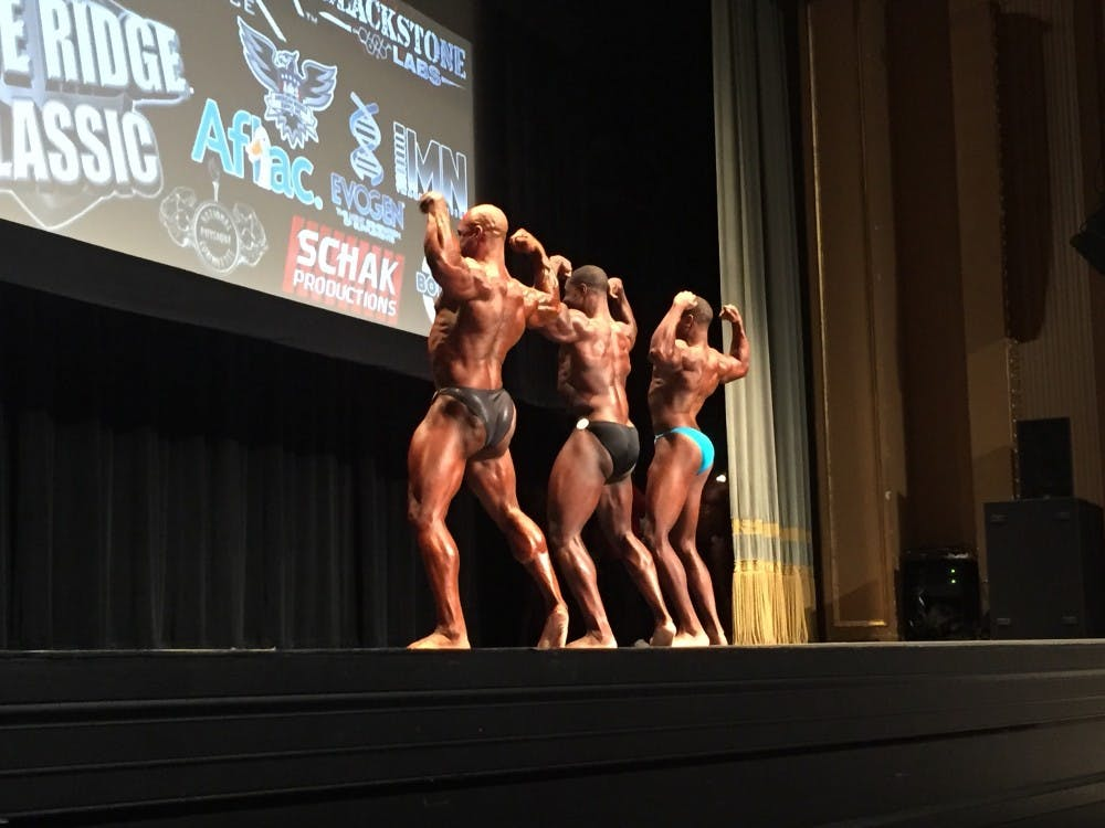 Male bodybuilders flex their backs for the judges.