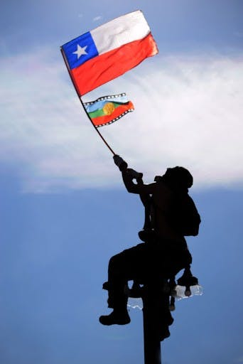 Person waving Chilean and Mapuche flags