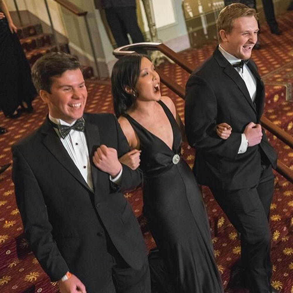 <p>Junior Regina Zhong walking with her escorts&nbsp;Kevin Cloyes (left) and&nbsp;Chris Okrasinski (right)&nbsp;at Ring Dance in 2015. | Photo courtesy of Regina Zhong.&nbsp;</p>