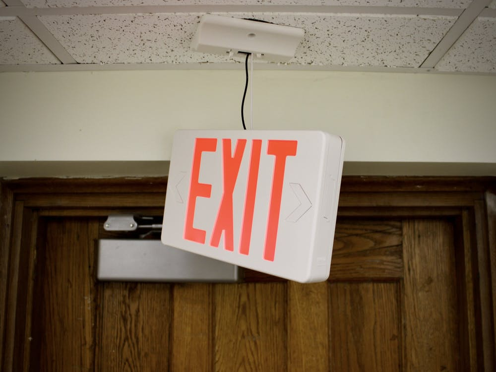 A broken exit sign dangles from the ceiling on the first floor of South Court.