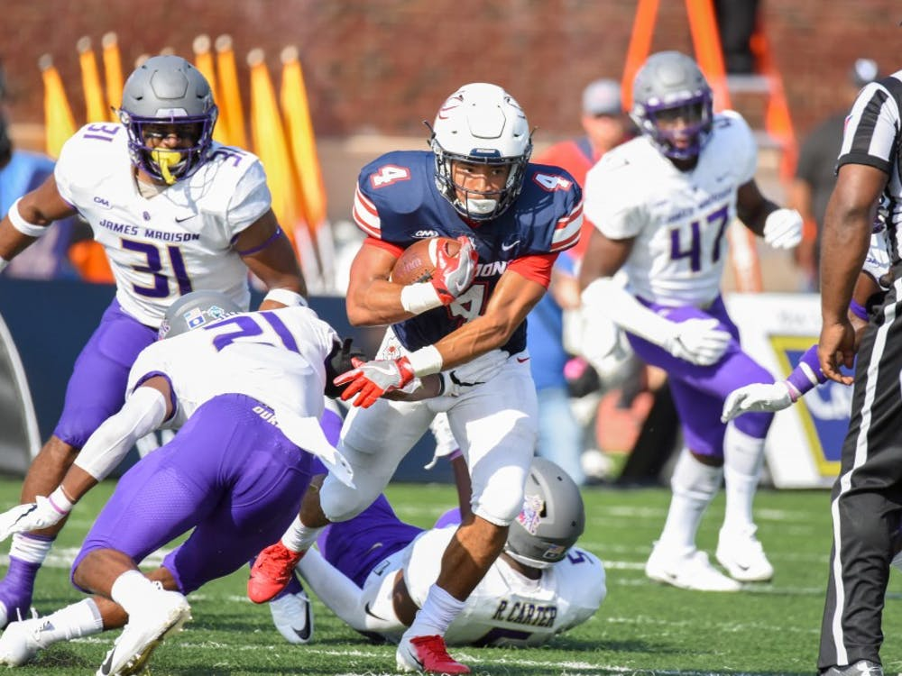 First-year running back Aaron Dykes runs through the JMU defense Saturday afternoon.