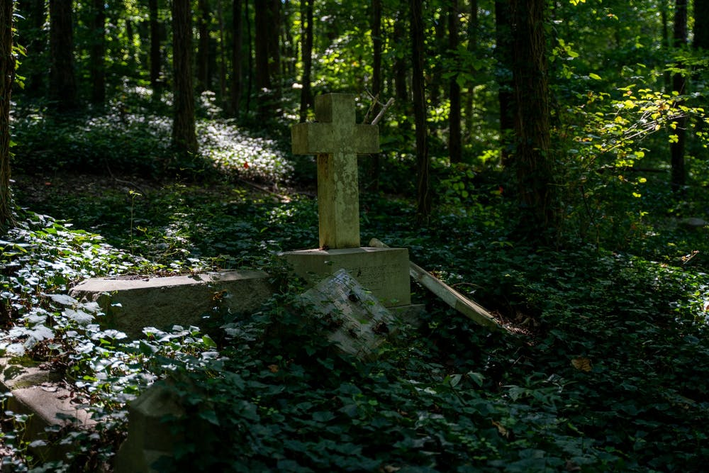 <p>As nature reclaims the land, a century-old cross stands alone among the ruins of several forgotten graves at the Evergreen Cemetery on August 31, 2019. &nbsp;</p>