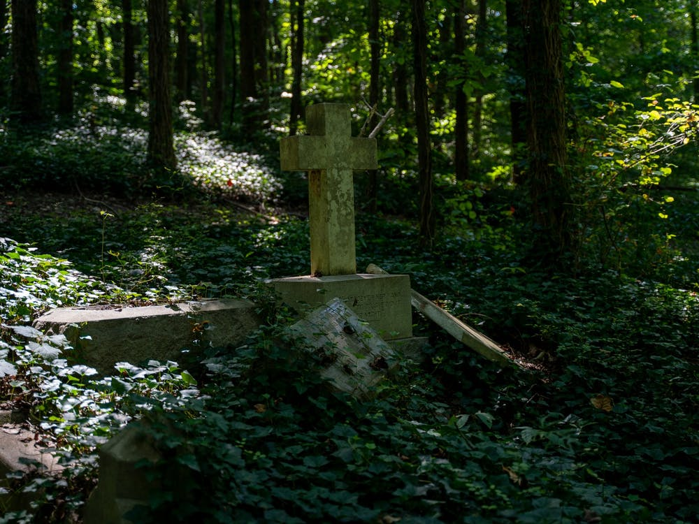 As nature reclaims the land, a century-old cross stands alone among the ruins of several forgotten graves at the East End Cemetery on August 31, 2019.