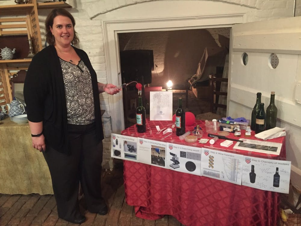 Biology professor Angie Hilliker demonstrates her method of wine extraction at the John Marshall House.