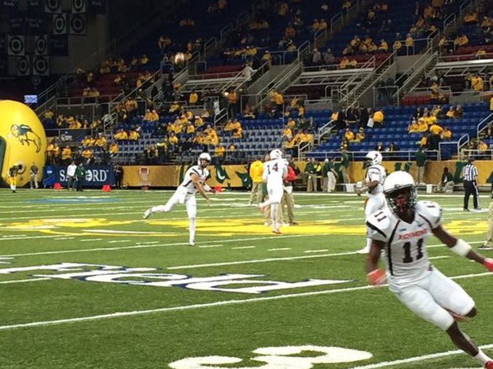 Quarterback Kyle Lauletta works with Reggie Diggs in warmups from the FargoDome. Photo courtesy of Spider Athletics.