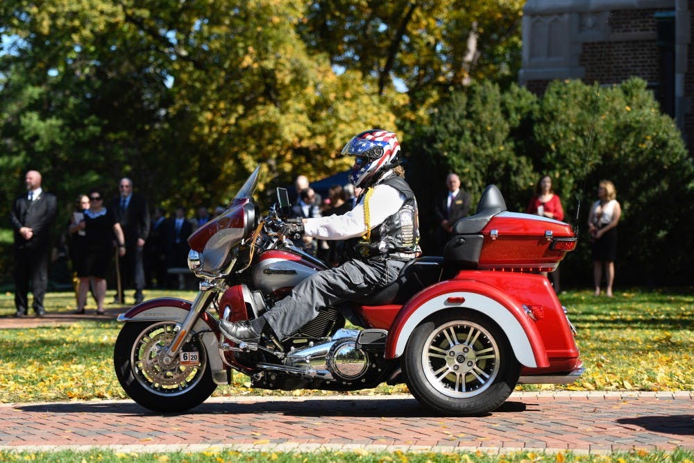 <p>Onlookers watch as a freedom rider makes his way into the Forum in celebration of E. Bruce Heilman's life on Sunday, Oct. 27, 2019.</p>
