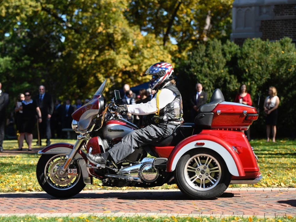 Onlookers watch as a freedom rider makes his way into the Forum in celebration of E. Bruce Heilman's life on Sunday, Oct. 27, 2019.