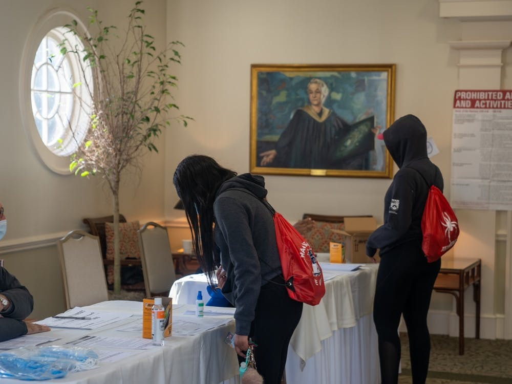 Two student-athletes sign in to vote among hand sanitizer, masks and COVID.