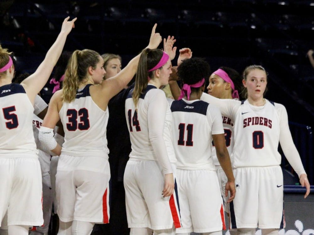 The women's basketball team huddlesduring a break.