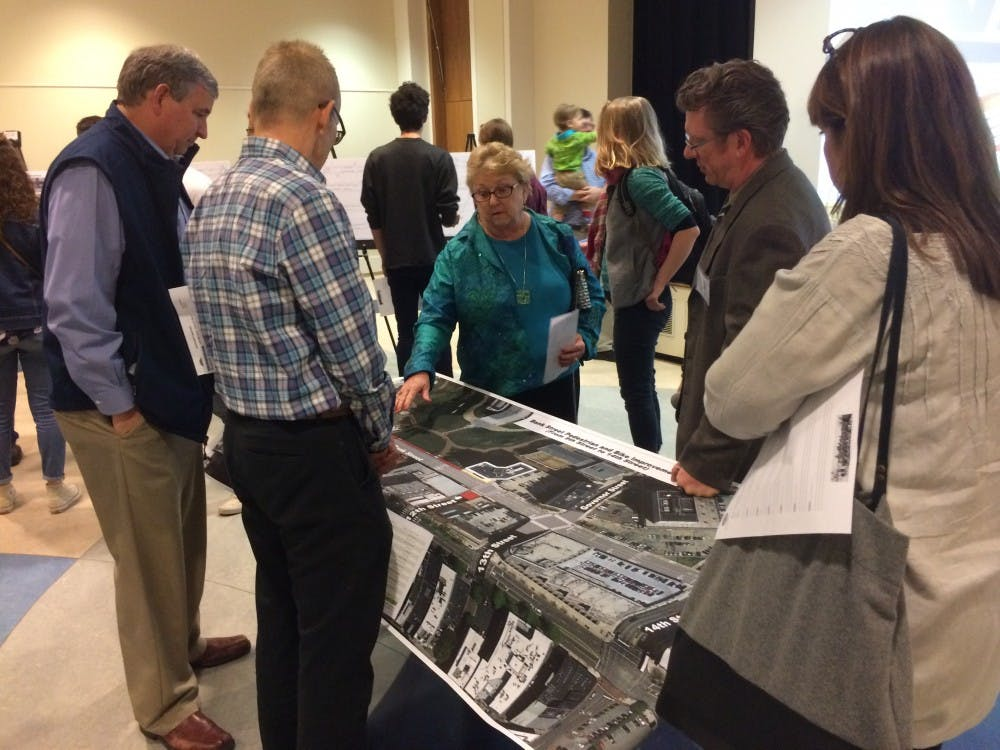 <p>Bike Walk RVA forum attendees&nbsp;look over a map of the new road designs, which plan to&nbsp;construct 25 miles of bike lanes throughout the city of Richmond.</p>