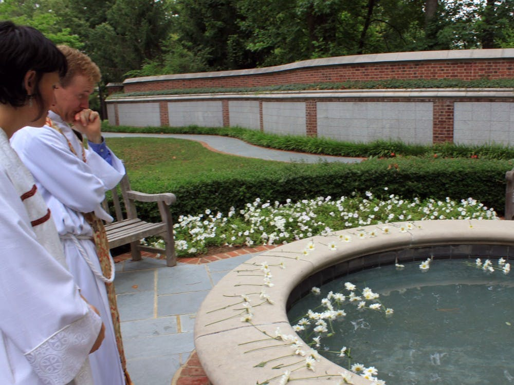 Rev. Craig Kocher, left, and associate chaplain Kate O'Dwyer Randall stand and reflect in front of a memorial pool filled with daisies in memory of Jamie and Paige Malone at the Cannon Memorial Chapel at the University of Richmond.