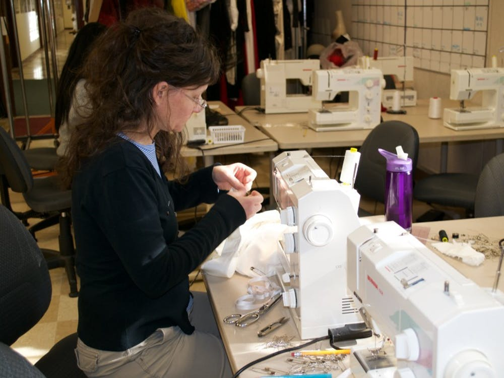 Heather Hogg, assistant director of costume, gets to work sewing a costume.