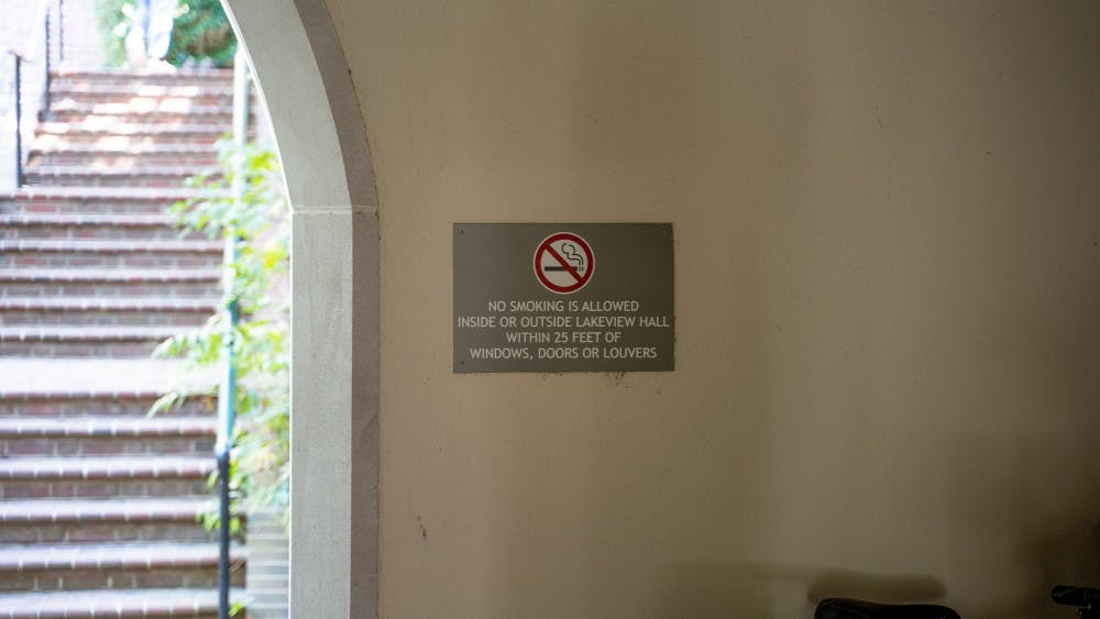 <p>A sign outside Lakeview Hall explains the distance a person must be from the building to smoke.</p>