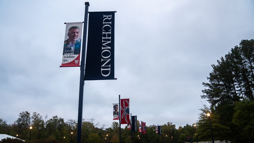 <p>University signs hung beside the River Road entrance glisten in the glow of the street lamps on a cloudy night.</p>