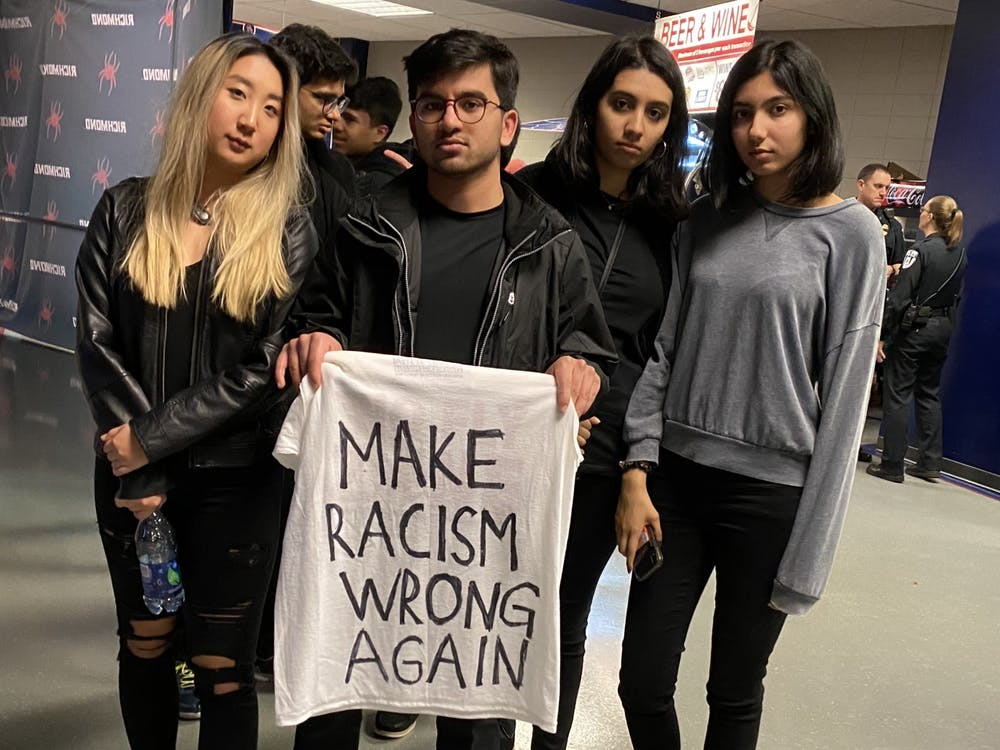 Student protesters pose with a sign after leaving the arena during the University of Richmond men's basketball game on Saturday, Jan. 25, 2020. Janis Lee, junior (left); Nasir Aziz, senior; Aamina Ahmed, junior; Aleena Ahmed, first-year.