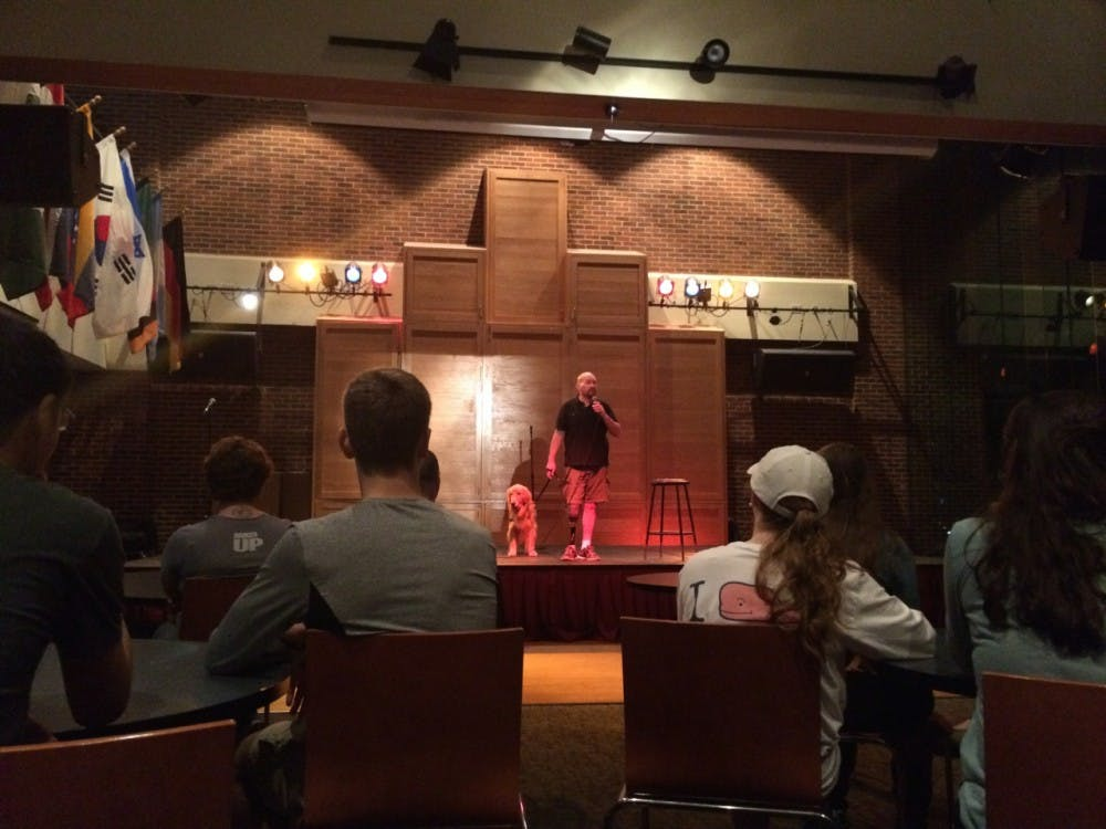 <p>Comedy warrior Joe Kashnow performs for Richmond students with his service dog.</p>