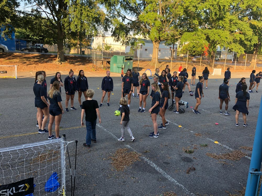 <p>Members of the University of Richmond women's soccer team teach street soccer to local elementary schoolers. <em>Photo courtesy of Street Soccer RVA</em></p>