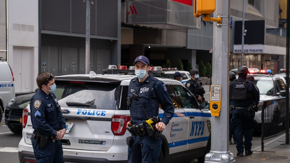 <p>&nbsp;An NYPD officer covers his face while posted at Times Square on April 5, 2020.&nbsp;</p>