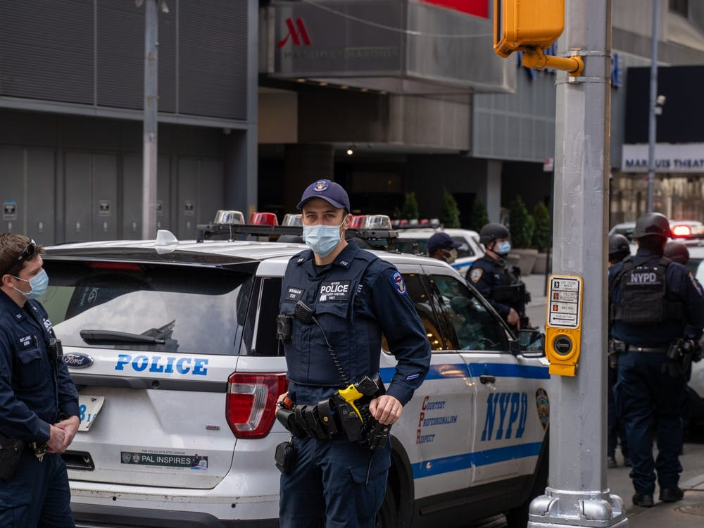 An NYPD officer covers his face while posted at Times Square on April 5, 2020.